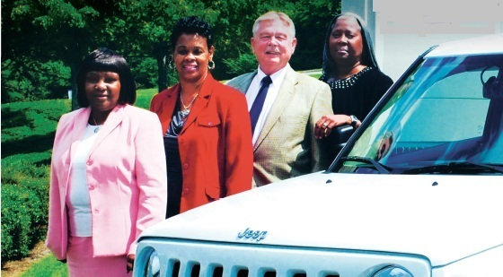 (L-R) Judith Jones, director of Administrative Services; Sherry Clay, fleet administrator 1; Chuck Kukal, supervisor, Fleet, Mail Center, and Administrative Services; and Beverly Williams, fleet administrator II, stand with a branded Jeep Patriot LTD.