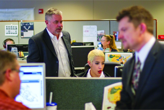 Brian Pheney and Monica Alvidrez discuss a fleet-related issue. Teamwork and communication are a big part of what keeps the DISH Network fleet moving. In the foreground are Tim Perkins (left) and Abe Stephenson.