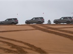 A line of gasoline-powered Discovery SUVs awaits the next dune.