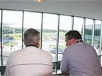 Two fleet managers look out on the Porsche Experience Center s track.